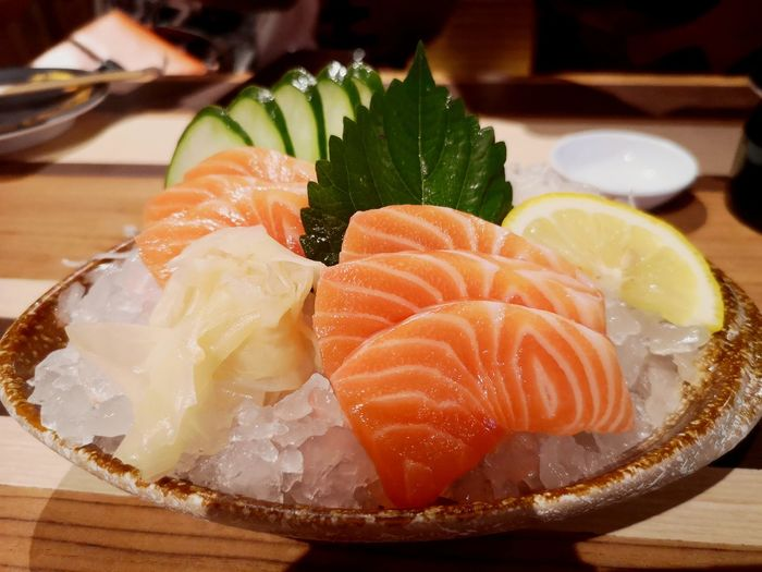 Close-up of sashimi with ice in plate on table