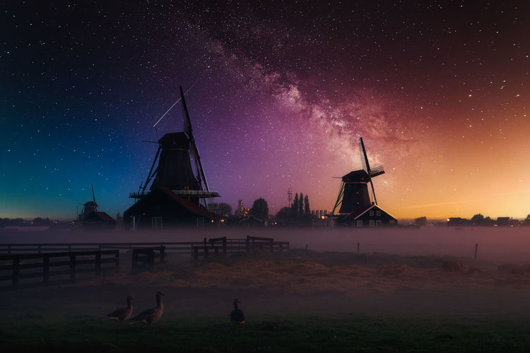 Traditional windmill against sky at night