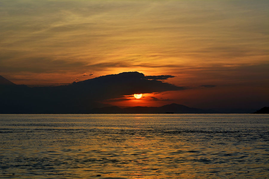eyes of sunrise Beauty In Nature Calm Cloud Cloud - Sky Dramatic Sky Idyllic Majestic Moody Sky Mountain Nature No People Non-urban Scene Orange Color Outdoors Remote Rippled Scenics Sea Sky Sun Sunrise Tranquil Scene Tranquility Water Waterfront