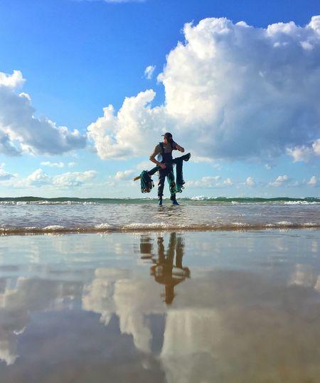 Man standing in water against sky