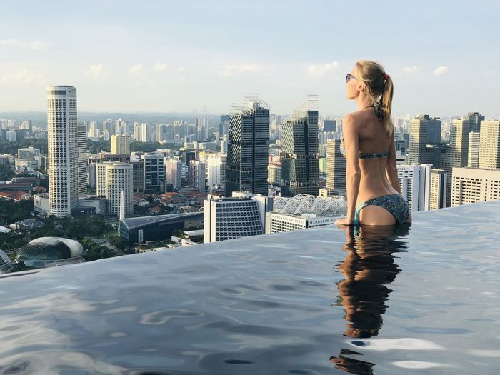 Woman swimming in pool by cityscape against sky