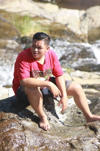 Young man looking away while sitting on rock