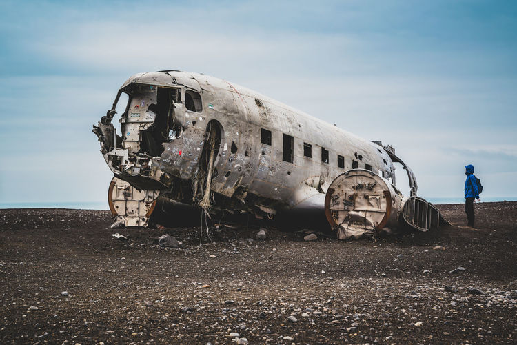 Man looking at abandoned airplane on field against sky