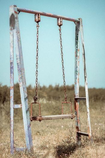 Abandoned swing against clear sky