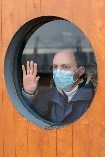 Man wearing mask while looking through window