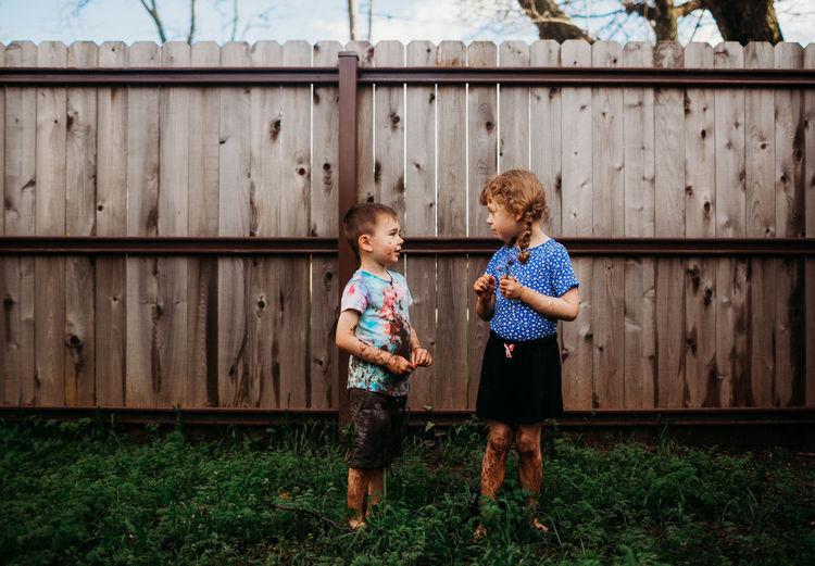 Full length of girl standing against fence