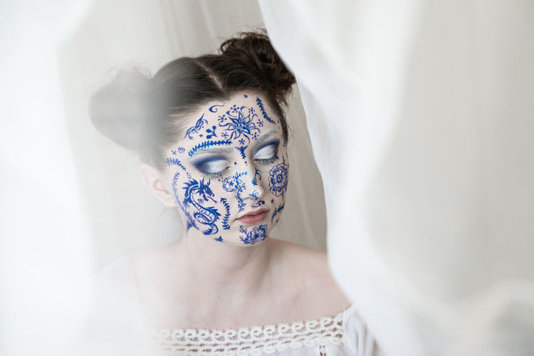 Woman with painted face and eyes closed by curtain at home