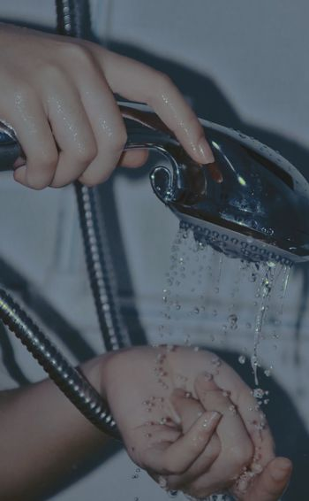 Close-up of woman using shower