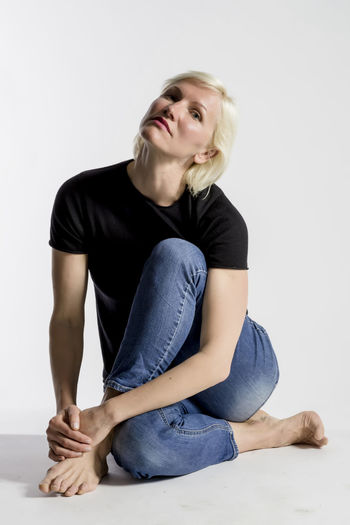 Portrait of attractive young blond woman sitting on floor and looking at camera isolated on white background One Person Studio Shot Casual Clothing Blond Hair Indoors  Front View Full Length Young Adult Sitting White Background Hair Young Women Lifestyles Portrait Women Cut Out Looking At Camera Jeans Hairstyle Beautiful Woman Contemplation Females Modelling Model Blonde Girl Lady Looking At Camera Sitting Ground Flooring