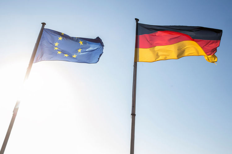 Low Angle View Of German And European Union Flags Against Sky