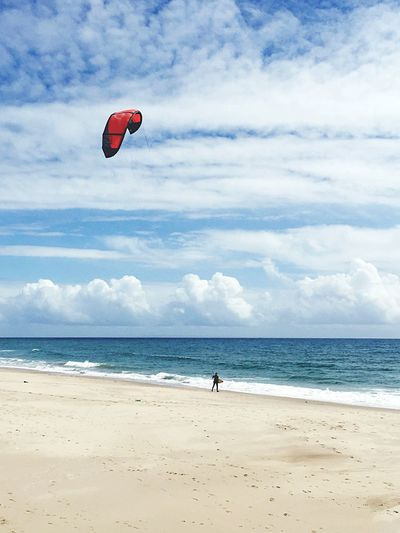 View Of Parachuting On Beach Against Clouds