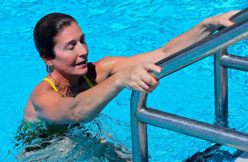 High Angle View Of Female Athlete Coming Out From Swimming Pool