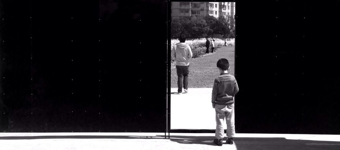 Rear view of boy standing in front of black gate
