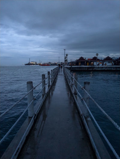 Pier over sea against sky at dusk