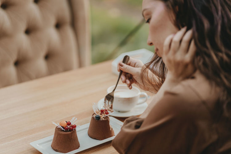 Midsection of woman having dessert in restaurant