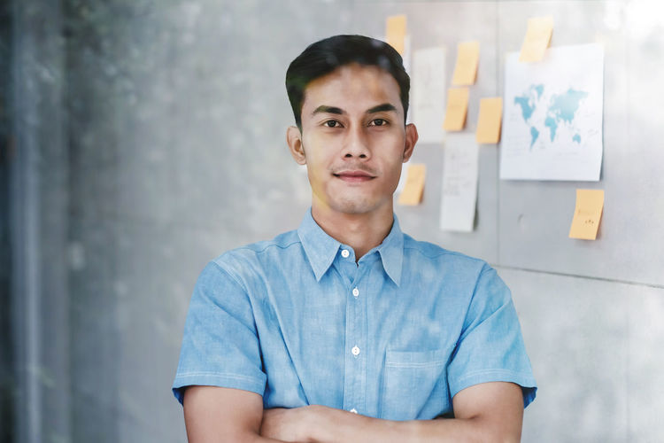 Portrait of Happy Young Asian Businessman standing by the Window Crossed Arms and Smiling in Office. Document's Data Plans and Project as background. Snap from Outside Building One Person Young Adult Portrait Front View Casual Clothing Looking At Camera Young Men Real People Waist Up Office Men Standing Business Person Indoors  Wall - Building Feature Males  Adult Creativity Confidence  Contemplation Designer  Creative Businessman