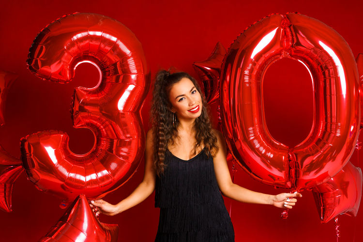 Young adult woman on the background of red balloons