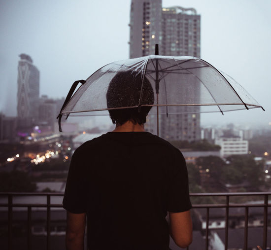 Rear view of man standing against cityscape during rain