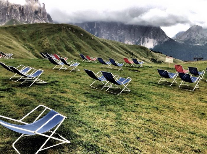 Empty foldable chairs on grassy field