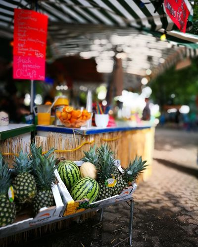 Pineapples and watermelons in crates for sale at street market