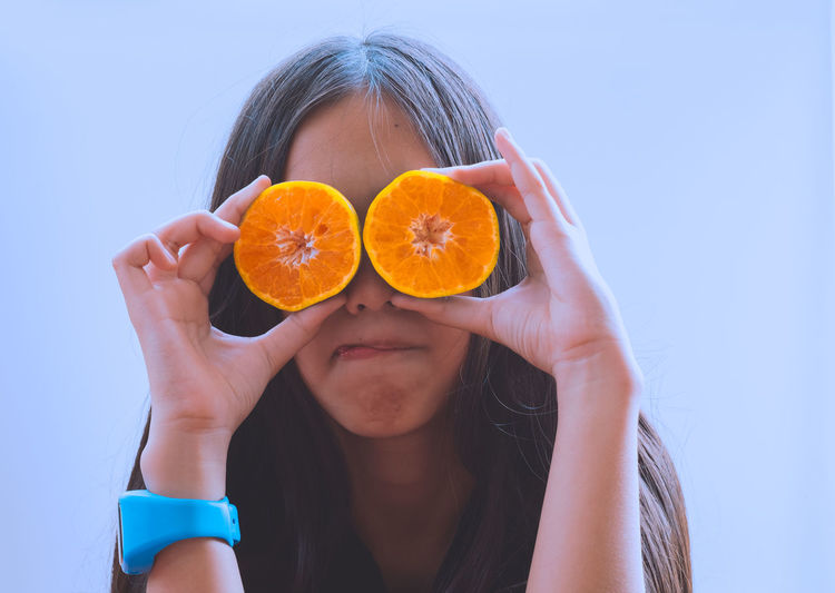 Close-Up Of Girl Holding Orange Slices Against Clear Sky