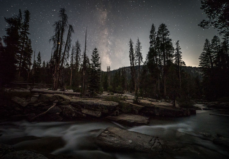 It was about time | JMT DAY 12 - MILKY WAY AT MOOSET Milky Way at moonset While the moon was traversing the heavenly body, the Milky Way was washed out quite a bit due to its close proximity. It was getting late, but I decided to wait longer for the galactic core to be seen. I really liked Bear Creek. Although I often find creeks challenging to work with in terms of capturing the galaxy, due to mostly dense, tall trees, this creek offered some clearings, and it was just a matter of patience that one may wait long enough, or till the right time to freeze that moment when the galaxy was erected vertically to his/her liking. Bear Creek was definitely one of those places where I would love to go back and explore the area more. I gotta admit that reaching the creek via Bear Ridge Trail from VVR wasn't a walk in the park. But the trail offered spectacular views of Mt. Hooper and other peaks as well as several stretches of Aspens along the trail itself. I even created a few waypoints telling myself that I would definitely come back in the fall. But for now it'll have to wait till next fall. The moon dropped over the ridge that was still being illuminated. The galaxy was risen vertically by then. It was about time. Bear Creek, Sierra National Forest, CA Tree Beauty In Nature Forest Scenics - Nature Tranquility Sky Tranquil Scene Nature No People Water Non-urban Scene Outdoors Landscape Milky Way Moonset Bear Creek, Sierra Nevada Stars Astrophotography
