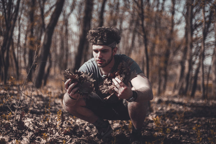 Young man holding dried leaves at forest