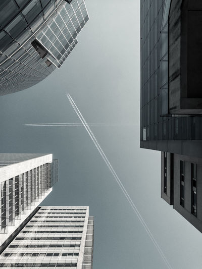 Directly Below Shot Of Buildings Against Vapor Trails In Clear Sky