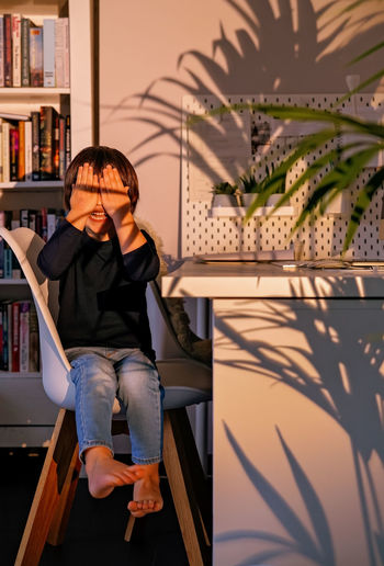 Woman sitting on book at home