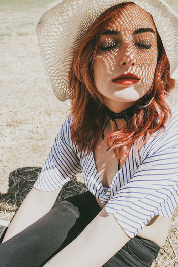 One Person Young Adult Real People Front View Leisure Activity Young Women Adult Lifestyles Hat Casual Clothing Women Portrait Beauty Clothing Sunlight Sitting Day Nature Hairstyle Beautiful Woman Hair Outdoors Sun Hat Contemplation Sunny