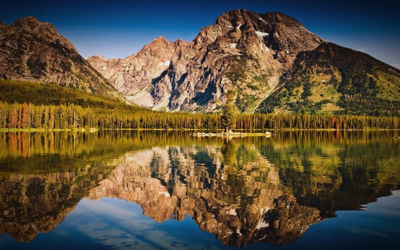 Scenic View Of Lake In Front Of Rocky Mountains