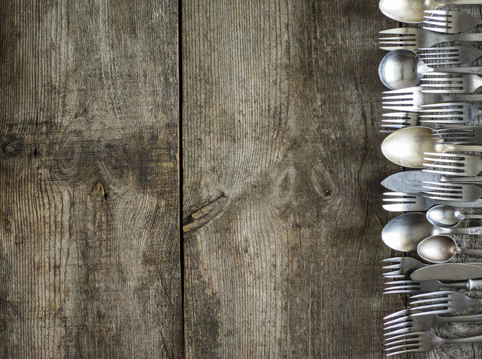 High angle view of old silverware on wooden table