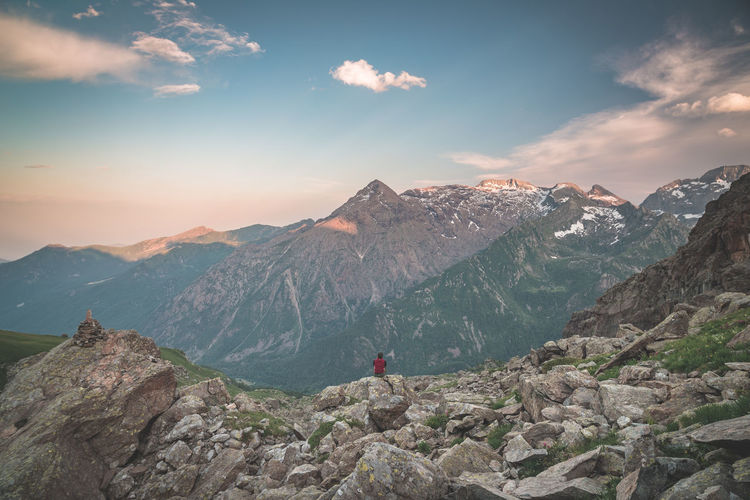 Mid distance view of hiker sitting on rock against mountain range during sunrise