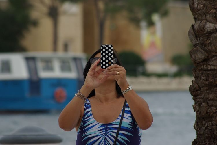Woman photographing through mobile phone in city