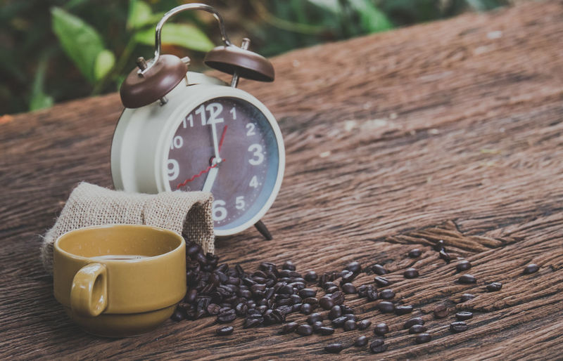 A brown alarm clock and coffee beans in a sack bag, on old wood table, selective focus Alarm Arabic Arabica Aroma Aromatic Background Bag Beans Beverage Break Breakfast Brown Business Cafe Caffeine Cappuccino Casual Clock Coffee Dark Design Energy Expresso  Fresh Gourmet Grain Growth Idea Lifestyle Meeting Mocha Modern Morning Mug Relax Restaurant Shop Success Symbol Table