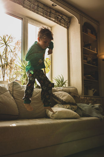 Boy looking through window at home