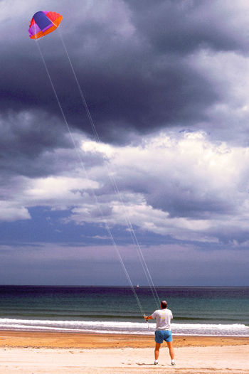 man, kite, beach. Beauty In Nature Casual Clothing Cloud Cloud - Sky Cloudy Day Enjoyment Full Length Fun Horizon Over Water Idyllic Kite, Flying Leisure Activity Lifestyles Nature Outdoors Scenics Sea Shore Sky Tranquil Scene Tranquility Vacations Water