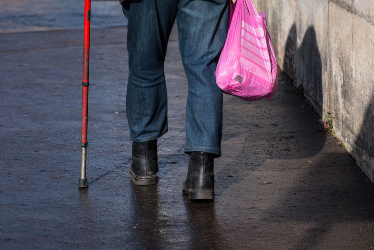 Low section of man walking with bag and cane on street