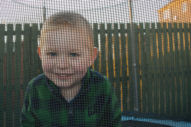 Portrait Of Smiling Boy Seen Through Netting