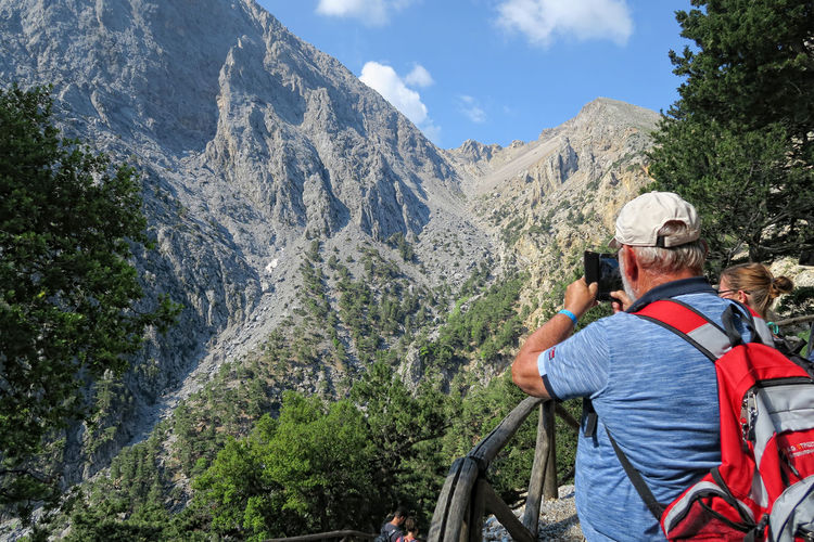 Samaria, Crete / GREECE May 25 2017: Man taking photo with mobile through while hiking on trail through Samaria gorge. (Crete, Greece). Adventure Backpack Canyon Crete Crete Greece Crete Island Gorge Greece GREECE ♥♥ Greece, Crete Hiker Hiking Hiking Adventures Hiking Trail Hikingadventures Landscape Mountain Mountain Range One Man Only One Person Photographing Real People Samaria Samaria Gorge Samaria Schlucht