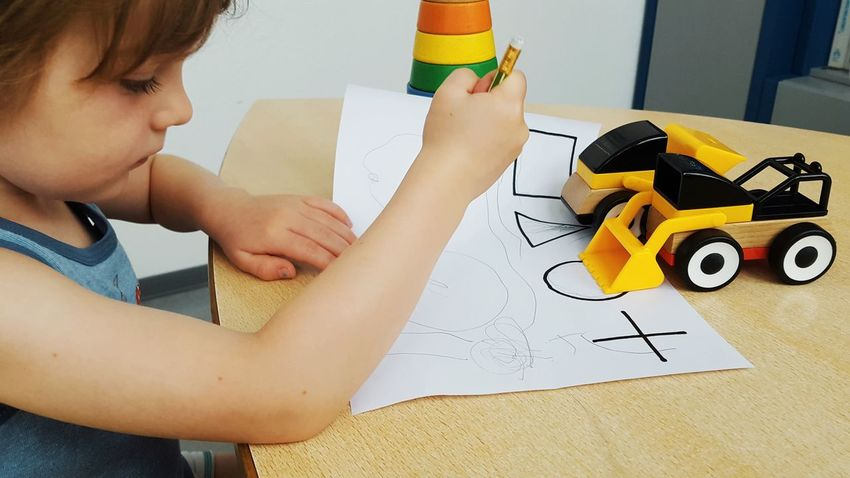 Boy Cars Childhood Close-up Colorful Day Desk Drawing Excavator Geometric Geometric Shape Holding Human Body Part Human Hand Indoors  One Person Paper Pediatrician Pediatrics People Real People Test Testing Toy Toys