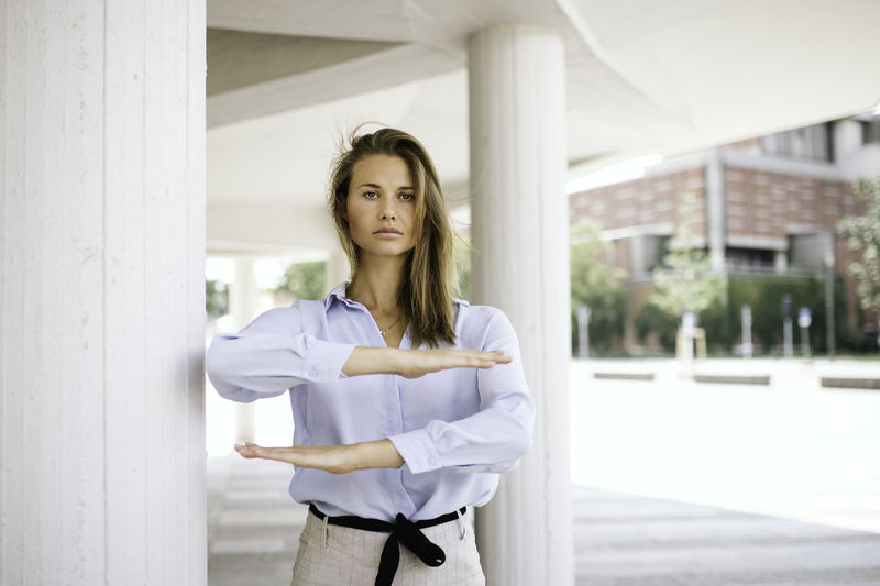 Portrait of young woman standing against white wall