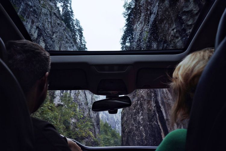 Mountain Rock Formation Sunroof Nature Canyon People Young Women Passenger Seat Headshot Car Interior Journey Car Road Trip Rear View Vehicle Interior Close-up Windshield Car Point Of View Steering Wheel Driving Windscreen RainDrop Vehicle Seat