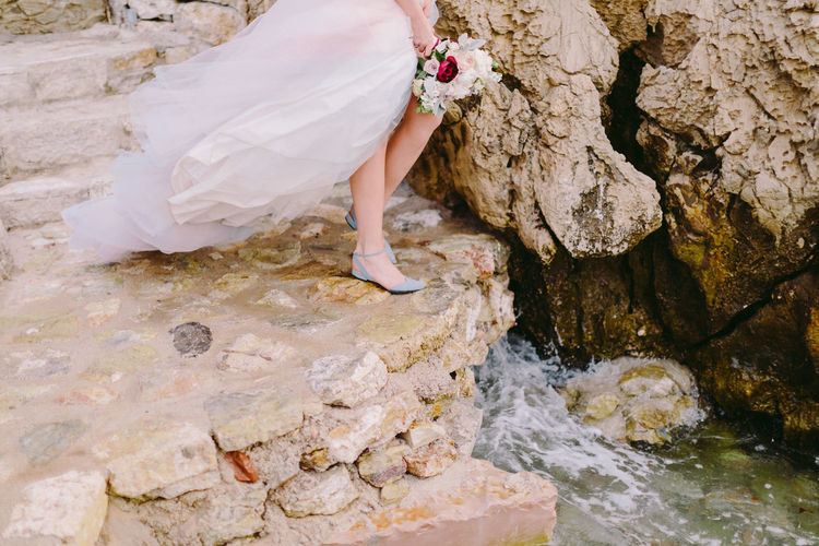 Low section of bride standing by rock