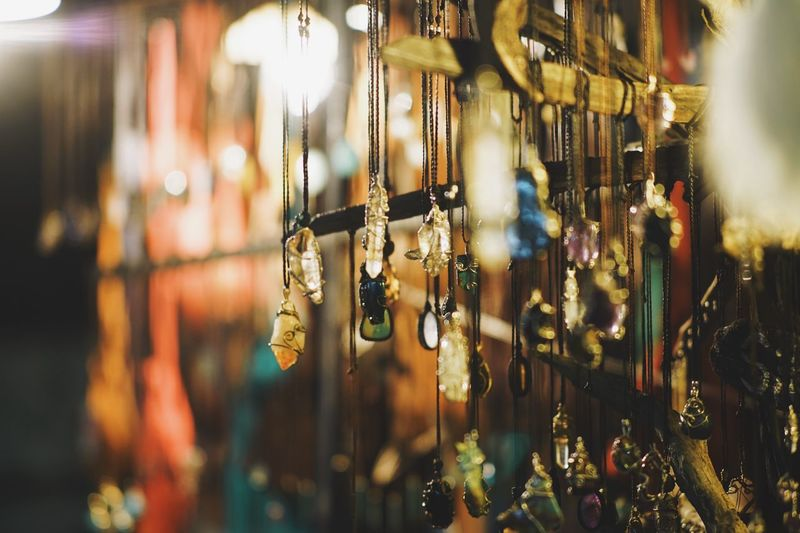 Close-up of decorations hanging for sale at market during night