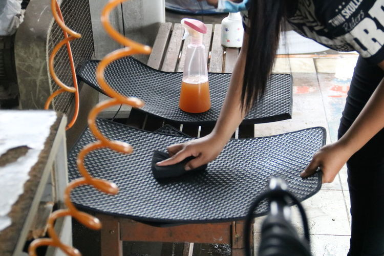 High angle view of woman cleaning equipment on bench