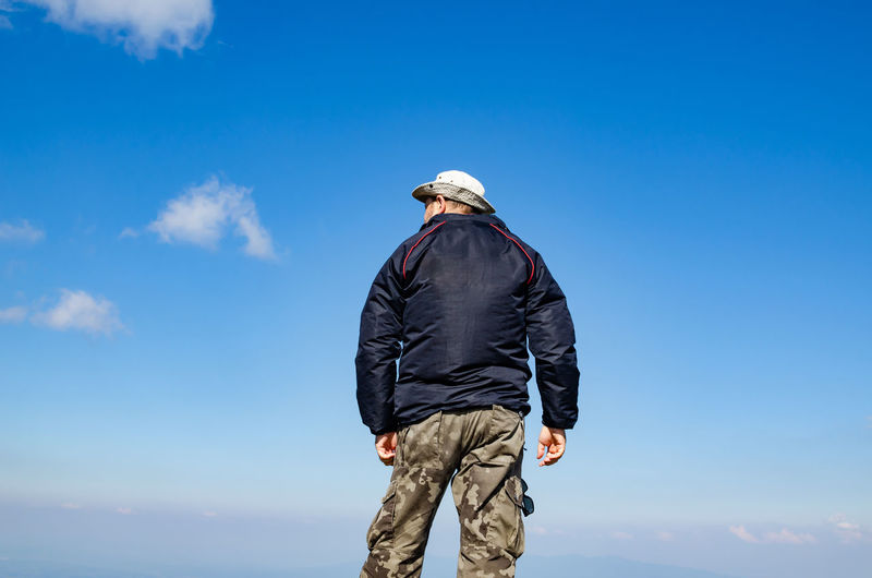 Rear view of man standing against blue sky