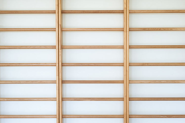Wooden ladders on white wall in gym