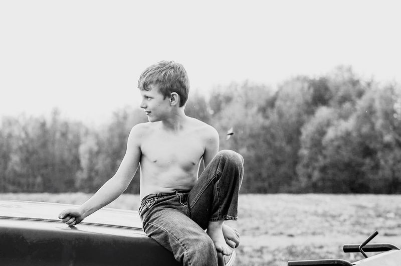 Full Length Of Shirtless Boy Sitting Against Sky