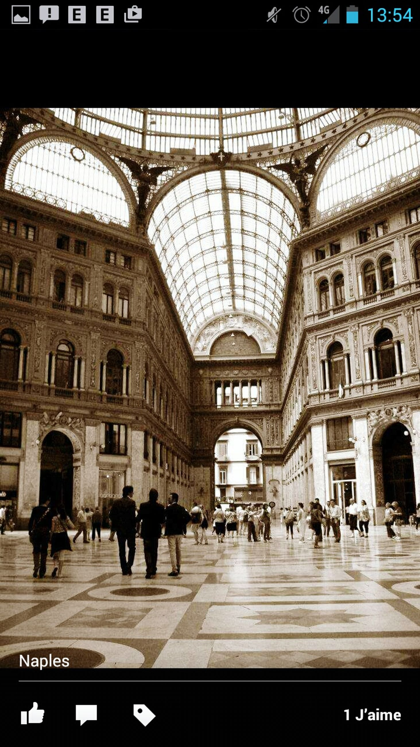 large group of people, architecture, built structure, indoors, men, person, arch, walking, building exterior, text, city life, travel destinations, lifestyles, travel, ceiling, city, railroad station, famous place, group of people